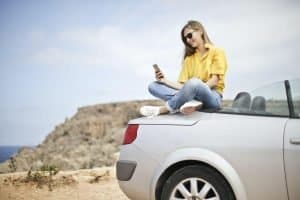 Woman sitting on tail end of car looking at phone
